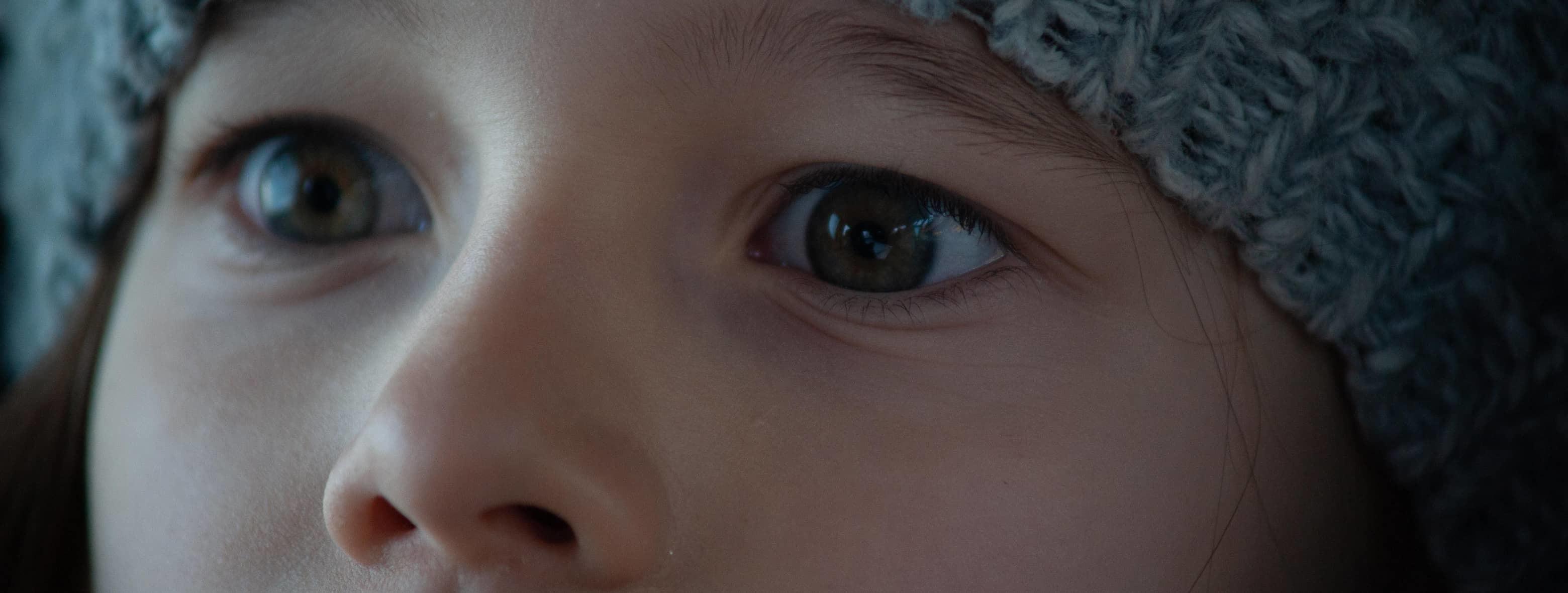Zbliżenie na oczy przerażonej dziewczynki, która właśnie ujrzała nadjeżdżającą z naprzeciwka ciężarówkę.